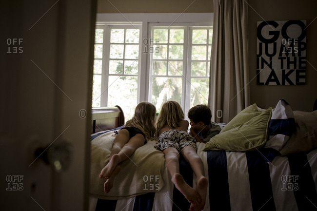 Three small children lying on a bed looking at the same thing