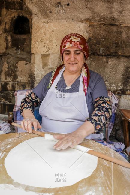Istanbul, Turkey - May 29, 2011: Woman rolling dough