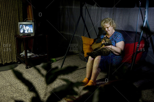 Torre del Lago, Italy - June 18, 2011: A woman pets her cat on a swing in her camp site