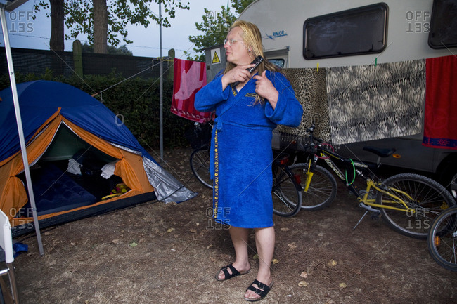 Torre del Lago, Italy - August 9, 2009: A woman combs her hair outside of her camper