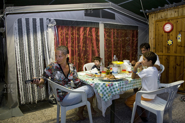 Torre del Lago, Italy - August 9, 2009: A family watches TV at dinner while camping