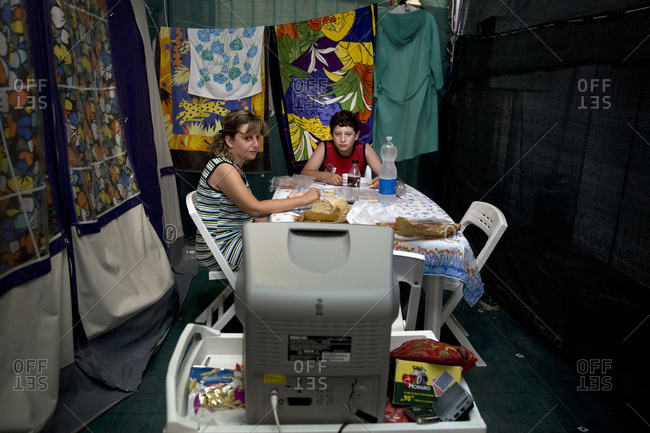 Torre del Lago, Italy - August 9, 2009: A mother and son watch television while camping
