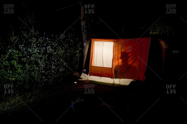 An illuminated tent sits in the darkness, Torre del Lago, Italy