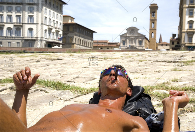 Florence, Italy - June 17, 2009: A man tans himself in the sun