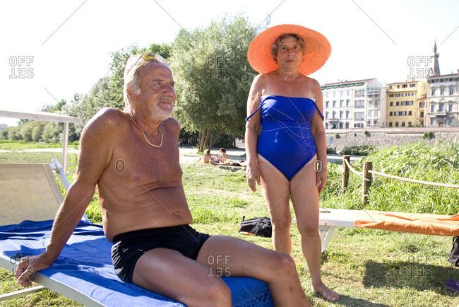 Florence, Italy - July 29, 2009: A man and a woman prepare to sunbathe