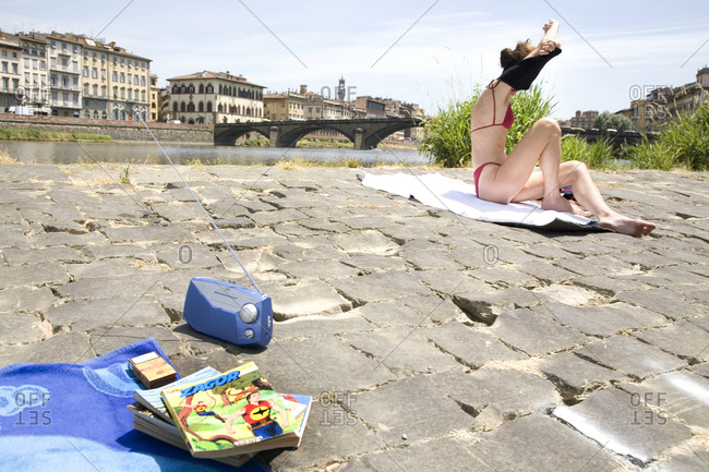 Florence, Italy - June 17, 2009: A woman takes off her shirt to sunbathe