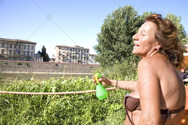 Florence, Italy - July 29, 2009: A woman mists herself on the banks of the Arno