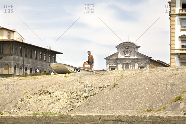 Florence, Italy - June 21, 2009: A man stands on his boat on the riverbank