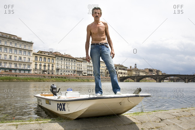 Florence, Italy - June 21, 2009: A man launches his boat into the Arno