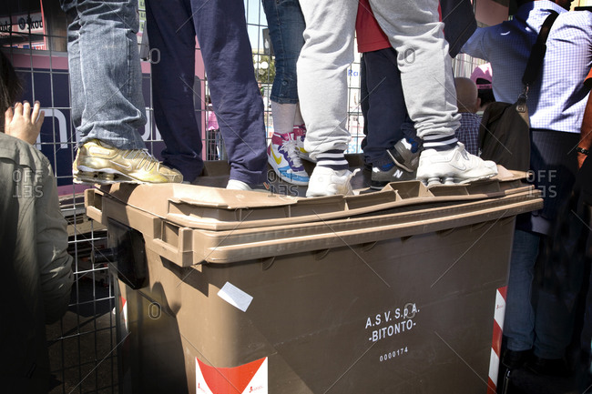 Spectators stand on a trash can to get a better view of a bike race, Bitonto, Italy, Giro d'Italia