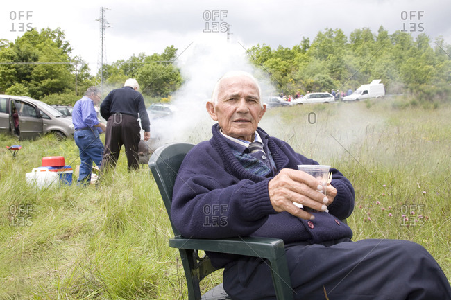 Lucera, Italy - May 19, 2010: An old man lounges in the grass waiting for a bike race to pass, Giro d'Italia