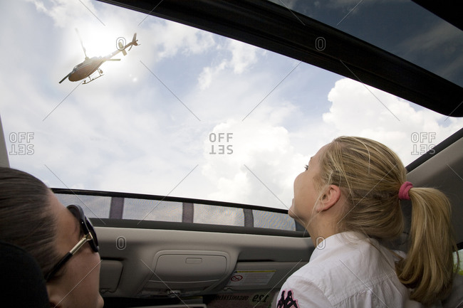 Lucera, Italy - May 19, 2010: A mother and daughter watch a helicopter from their sunroof, Giro d'Italia