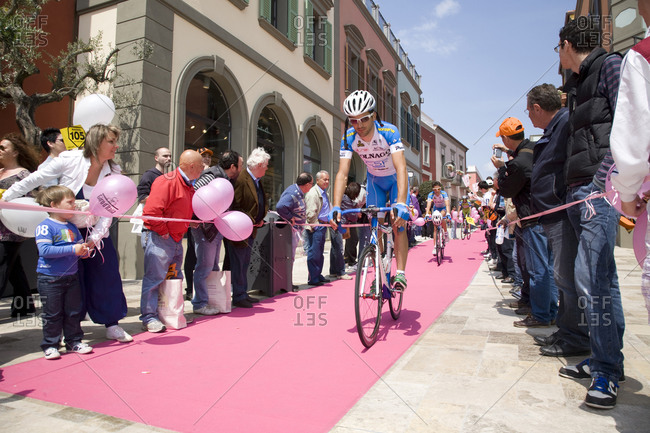 Città Sant'Angelo, Italy - May 20, 2010: Cyclists pass by crowds in a city street, Giro d'Italia