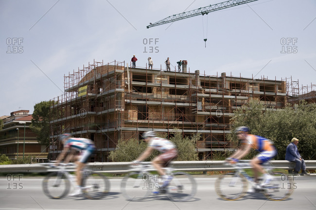 Cesenatico, Italy - May 20, 2010: Cyclists pass by a construction site, Giro d'Italia