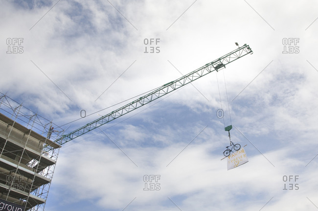 A fan hangs a poster off of a crane during a bike race, Giro d'Italia