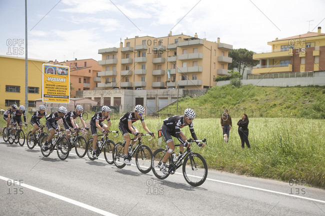 Cesenatico, Italy - May 21, 2010: A line of cyclists ride past apartment buildings, Giro d'Italia