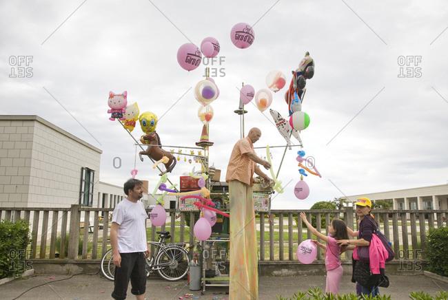 Cesenatico, Italy - May 21, 2010: A man on stilts hands a balloon to a little girl, Giro d'Italia