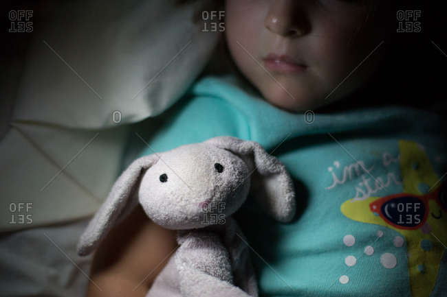 Little girl sleeping with a toy bunny