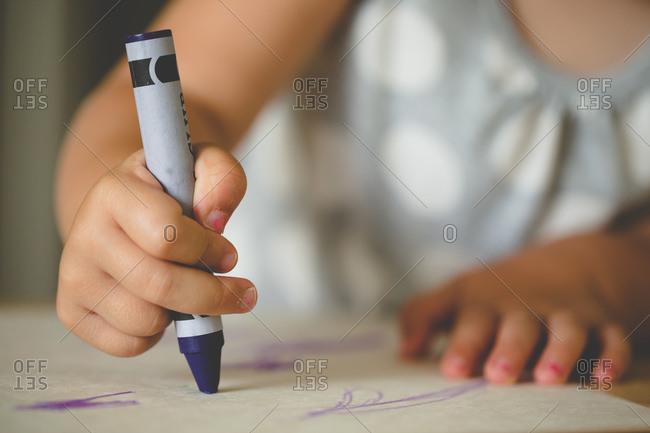 Close up of girl doodling with a crayon