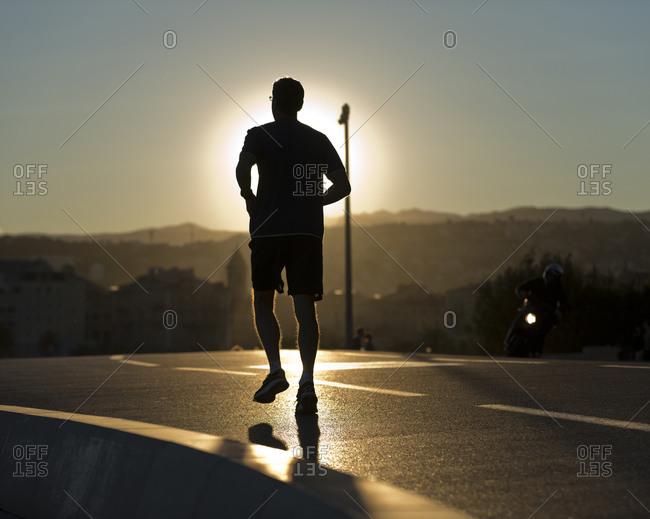 Man running on Rauba Capeu at sunset, Nice, France