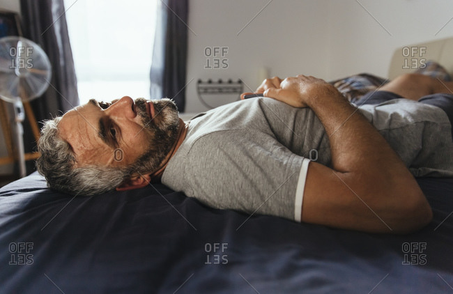 Pensive man lying on his bed at daytime