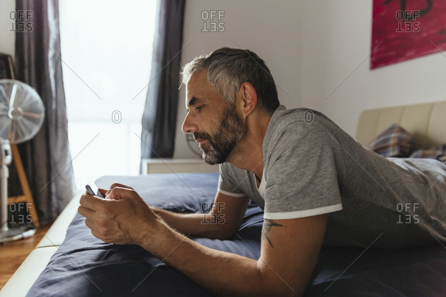 Man lying on his bed using his smartphone
