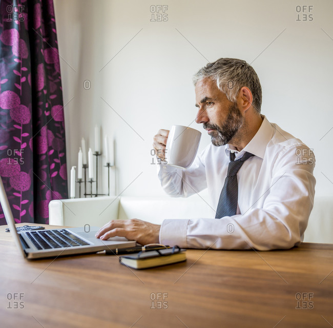 Portrait of businessman working at home office drinking coffee
