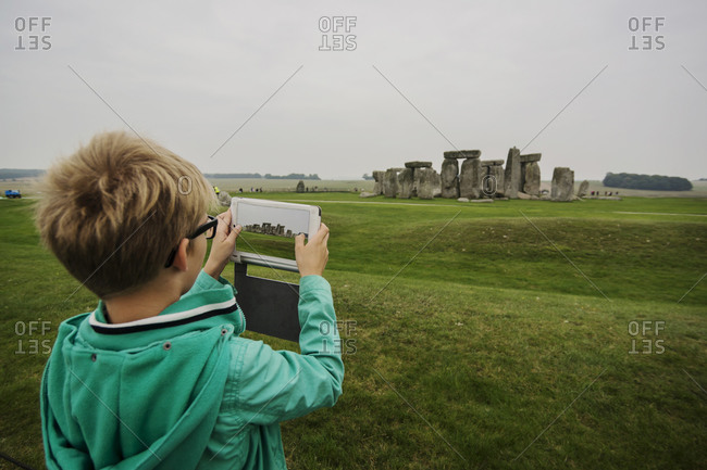 Boy photographing Stonehenge with his digital tablet
