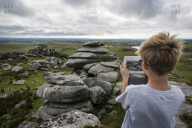 Boy photographing landscape at Bodmin Moor with his digital tablet
