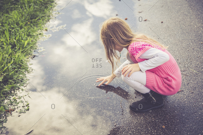 Little girl playing with water of a puddle