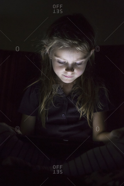 Portrait of little girl sitting in darkness using digital tablet