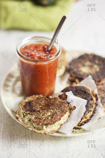 Dish of zucchini fritters and glass of tomato sauce