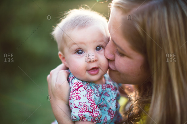 Mother kissing baby outside