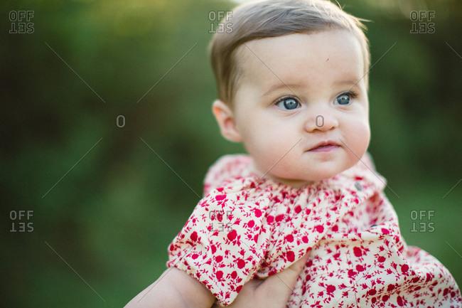 Baby girl held in hand outside