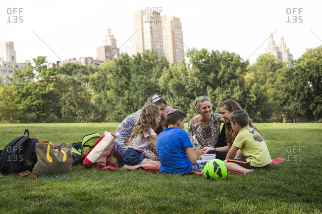 A group of kids on a picnic blanket in a park