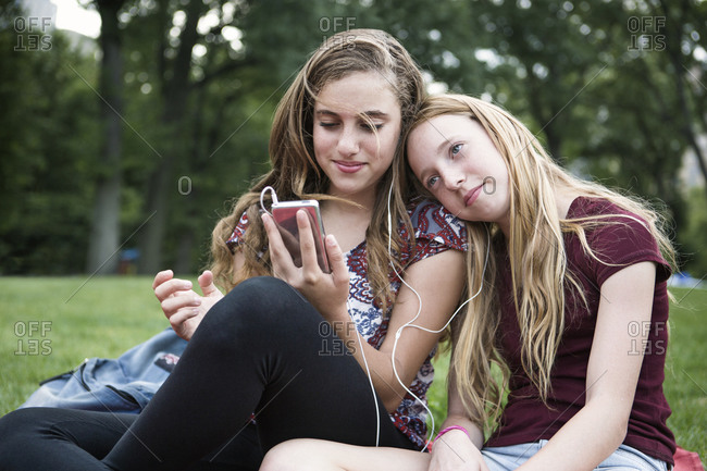 Two girls sharing headphones in a park