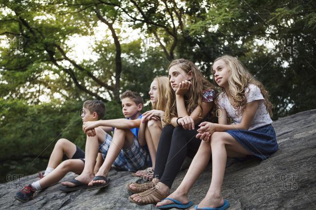 Five kids sitting on a rock