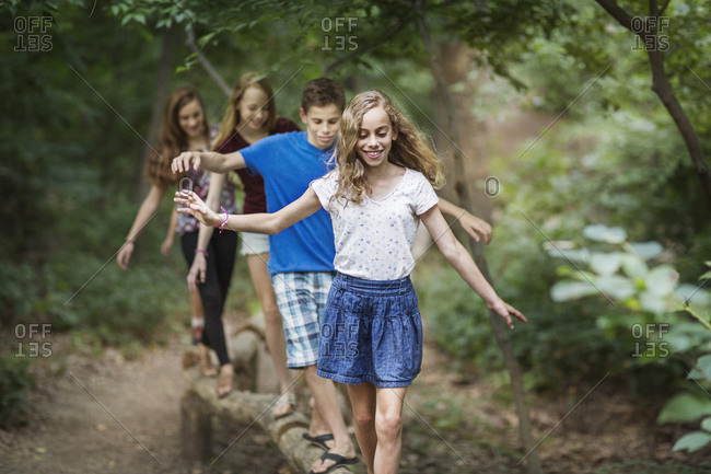 Four adolescents walk on a balance beam in the woods