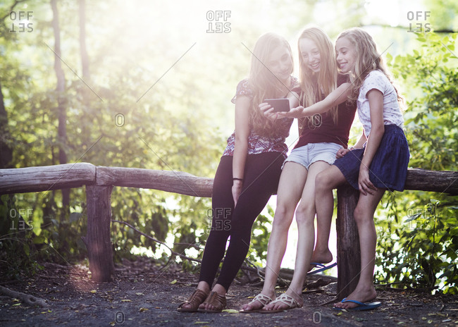 Three girls take a selfie in the woods