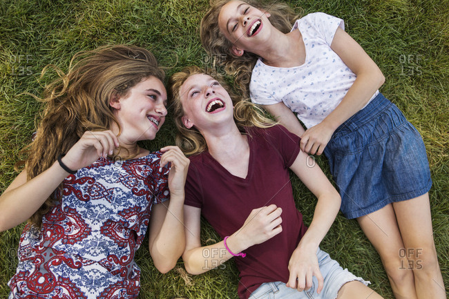 Three adolescent girls laughing in the grass