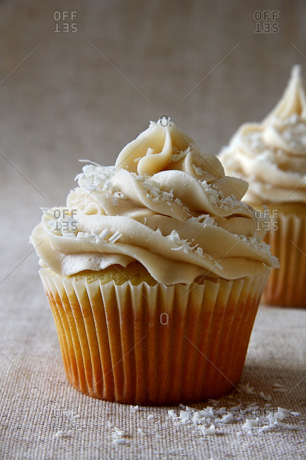 Close up of a vanilla cupcake topped with buttercream icing and white chocolate shavings