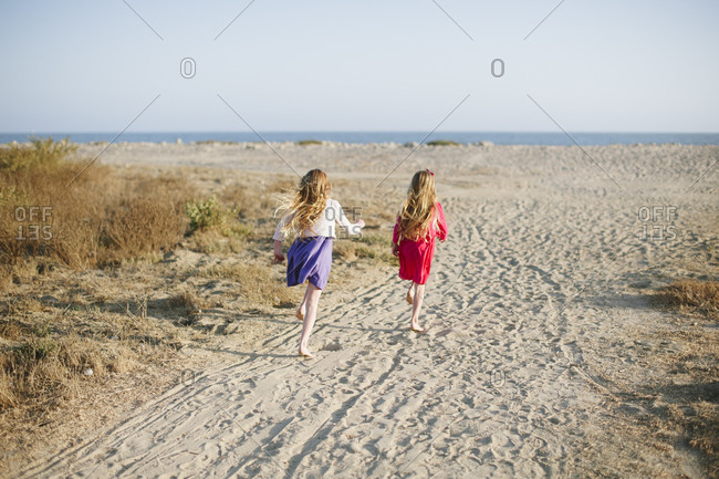Two little girls running to the beach