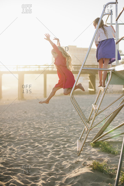 Two little girls playing on lifeguard tower ladder