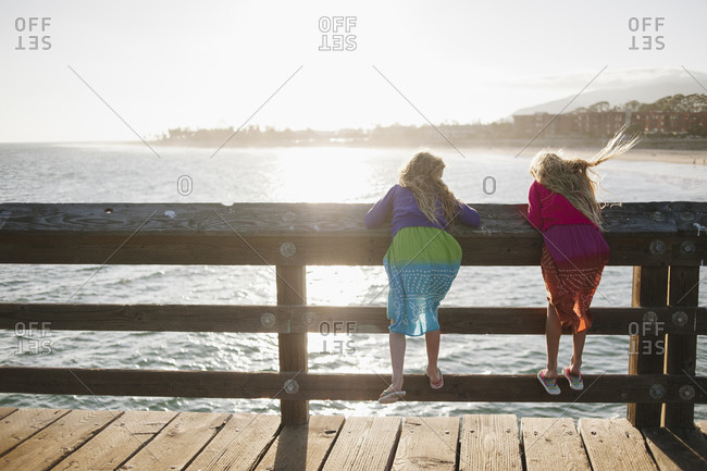 Two little girls looking over the railing of a pier