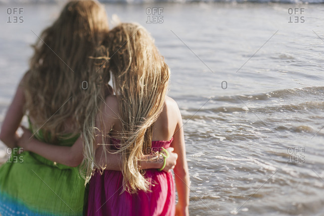 Two little girls hug and look at the surf
