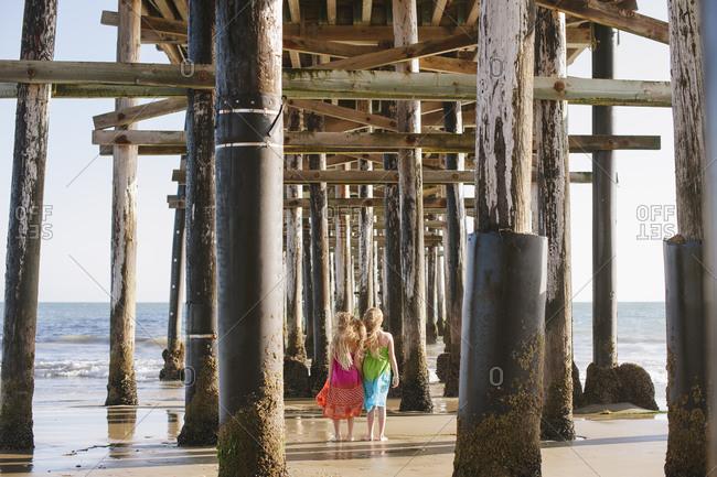 Two little girls walking under a pier