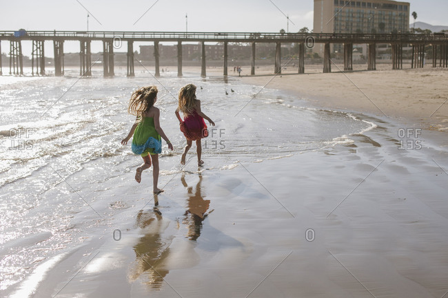 Two little girls running in the surf towards a pier