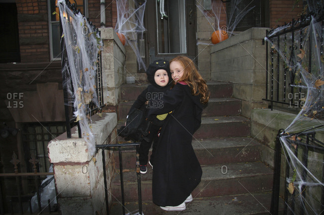Young girl hugging her brother in Halloween costume