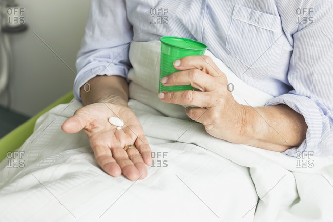 Patient in hospital holding cup and pills