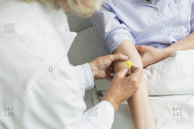 Doctor inserting infusion needle into patient's arm